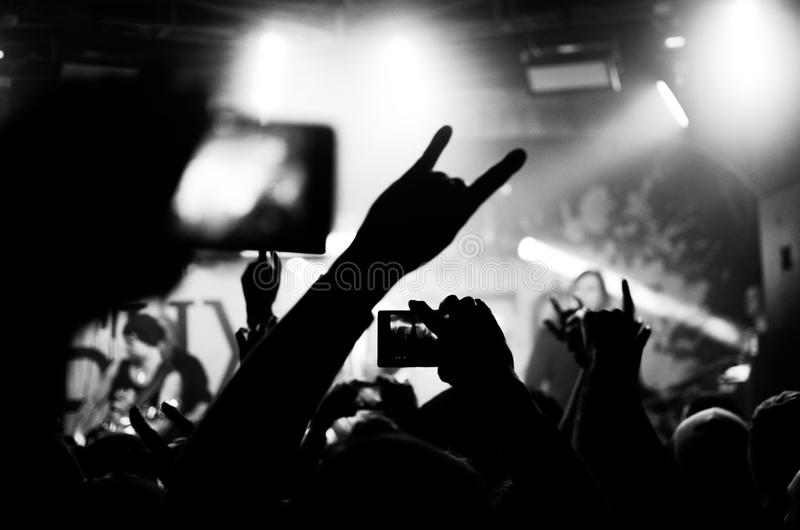 Silhouettes concert. Silhouettes of people in a bright in the pop rock concert in front of the stage. Hands with gesture Horns. That rocks. Рarty in a club stock images