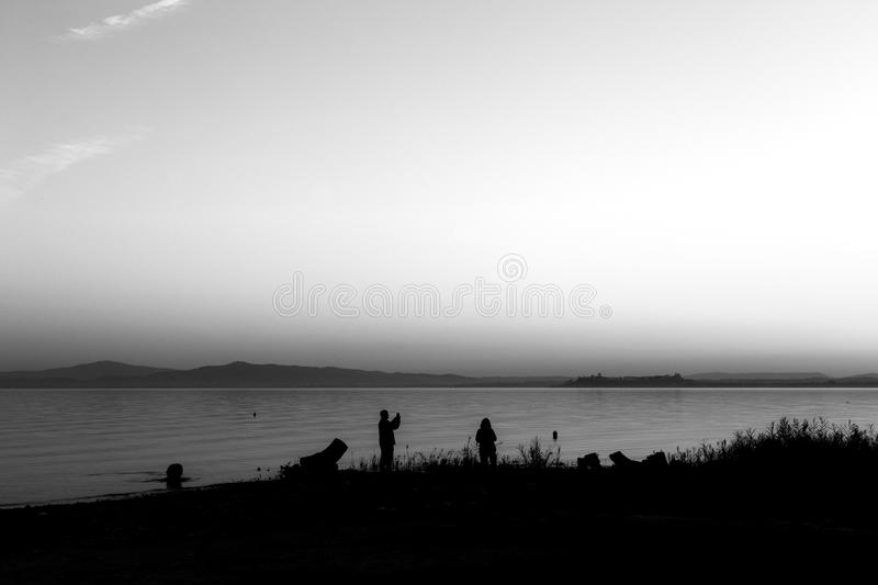 Silhouettes of a couple on a lake shore, taking photos of sunset stock photo