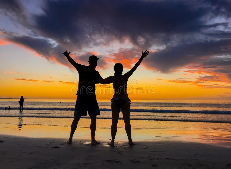 Silhouettes of couple in love at beach sunset celebrating freedom and love royalty free stock images