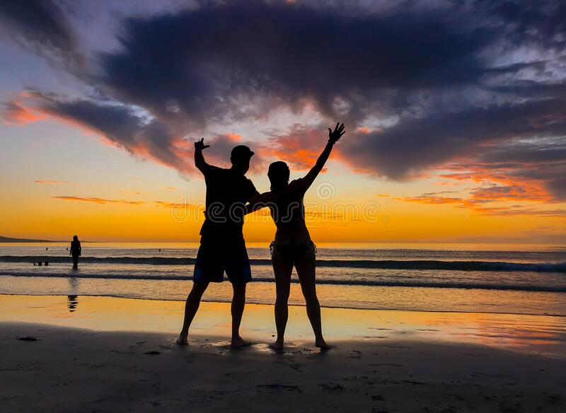 Silhouettes of couple in love at beach sunset celebrating freedom and love stock photography