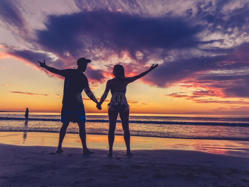 Silhouettes of couple in love at beach sunset celebrating freedom and love royalty free stock image