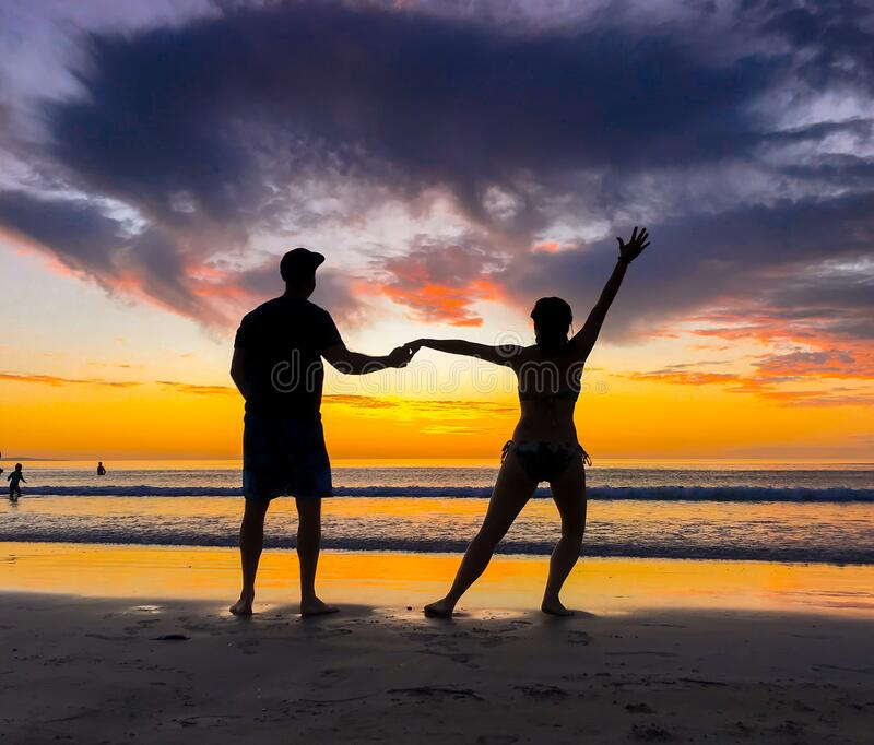 Silhouettes of couple in love at beach sunset celebrating freedom and love stock image