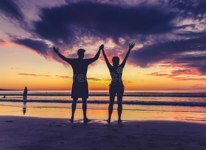 Silhouettes of couple in love at beach sunset celebrating freedom and love stock photos