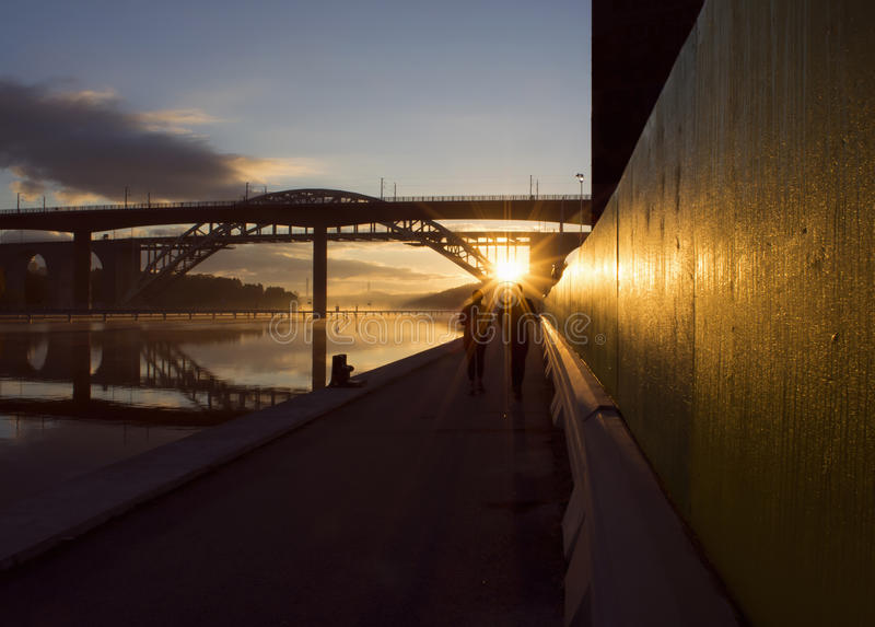 Silhouettes of couple running at beautiful, early dawn under a bridge. Silhouettes of a couple running an early morning, sun just rising. Urban landscape by stock images