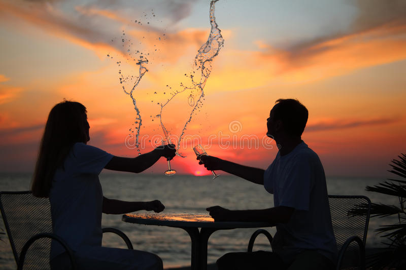 Download Silhouettes Of Couple Splash Out Drink From Glass Stock Photo - Image: 11411490