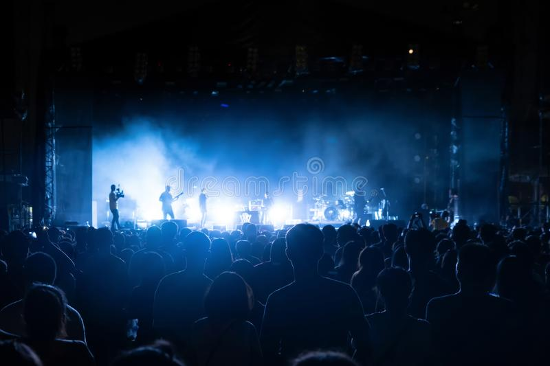 Silhouettes of crowd, group of people, cheering in live music concert in front of colorful stage lights.  royalty free stock photo