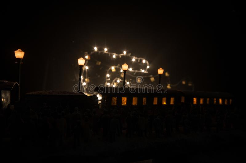 Silhouettes of a crowd standing at old vintage train on foggy background. Selective focus. Creative artwork decoration with toy. Train royalty free stock image