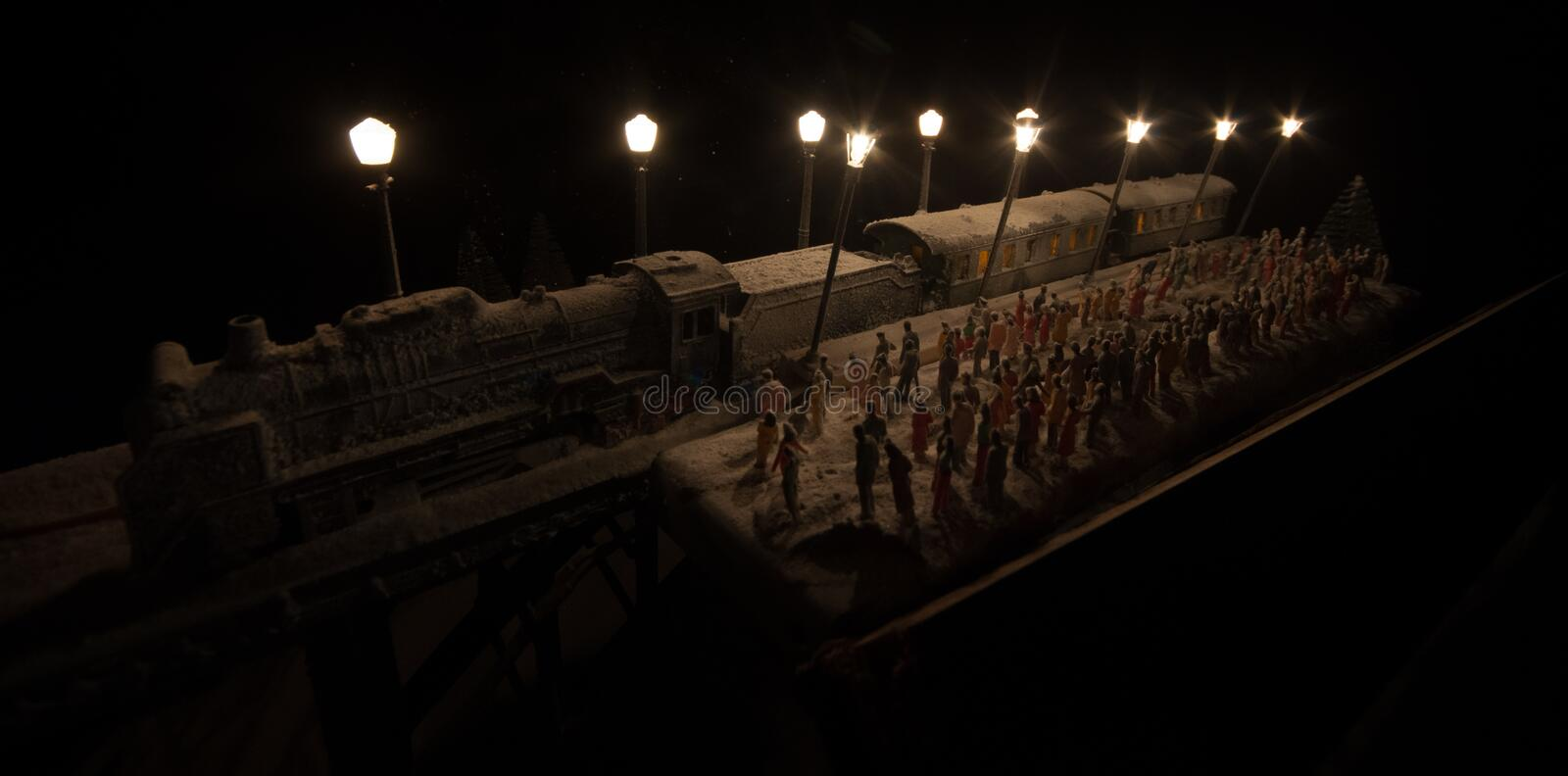 Silhouettes of a crowd standing at old vintage train on foggy background. Selective focus. Creative artwork decoration with toy. Train stock photography