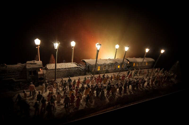 Silhouettes of a crowd standing at old vintage train on foggy background. Selective focus. Creative artwork decoration with toy. Train royalty free stock photos