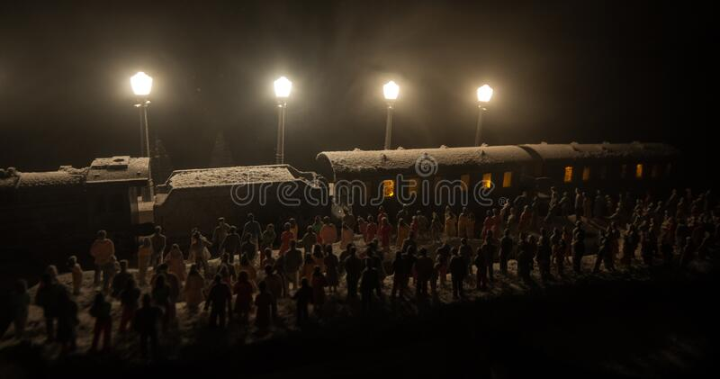 Silhouettes of a crowd standing at old vintage train on foggy background. Selective focus. Creative artwork decoration with toy. Train stock photo