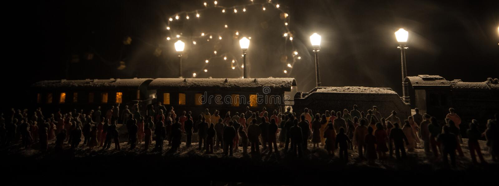 Silhouettes of a crowd standing at old vintage train on foggy background. Selective focus. Creative artwork decoration with toy. Train stock images