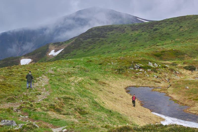 Silhouettes d'hommes en brouillard Hausse de déplacement d'hommes en montagnes image stock