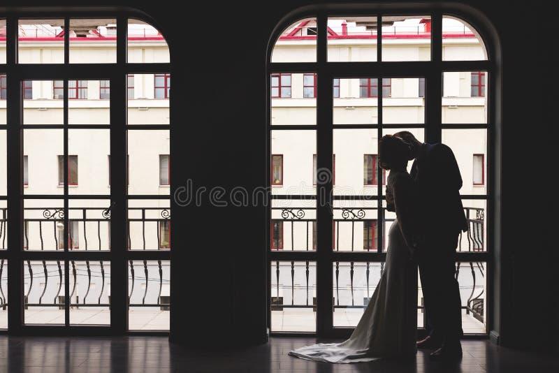 Silhouettes d'un homme dans un costume et d'une femme dans une robe et avec un bouquet des fleurs embrassant et s'étreignant proc images libres de droits