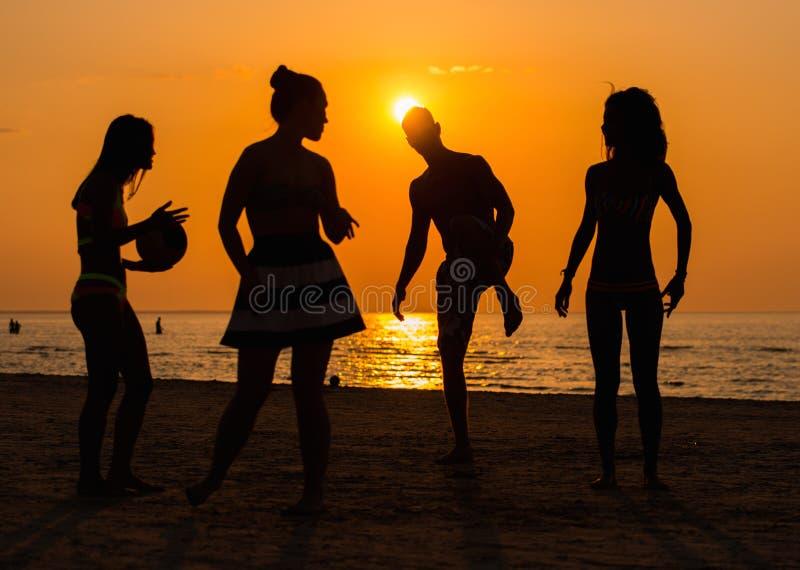 Silhouettes d'un peuple ayant l'amusement sur une plage photos stock