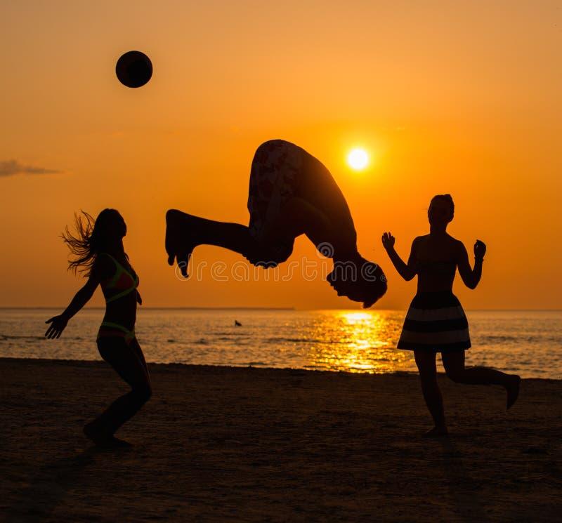 Silhouettes d'un peuple ayant l'amusement sur une plage photographie stock libre de droits