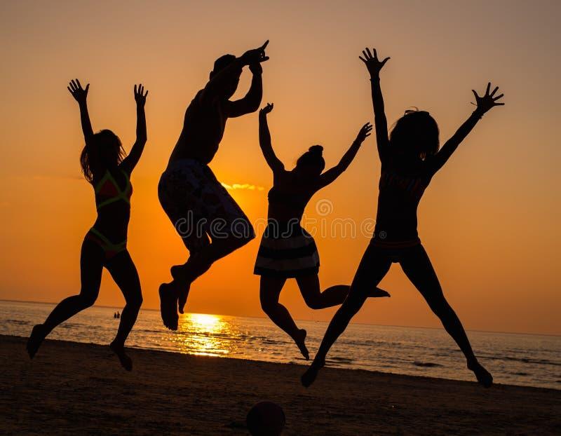 Silhouettes d'un peuple sur une plage images stock