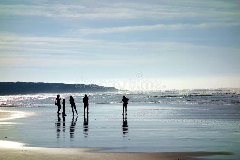 Silhouettes d'une famille sur la plage images libres de droits