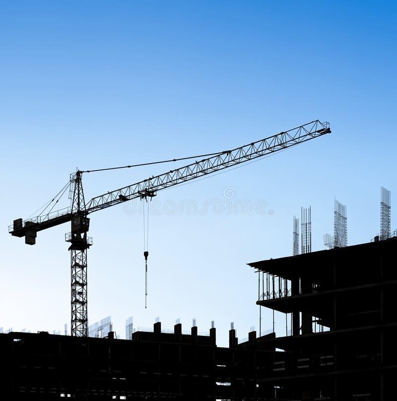Silhouettes d'une grue et d'un bâtiment de construction photo stock
