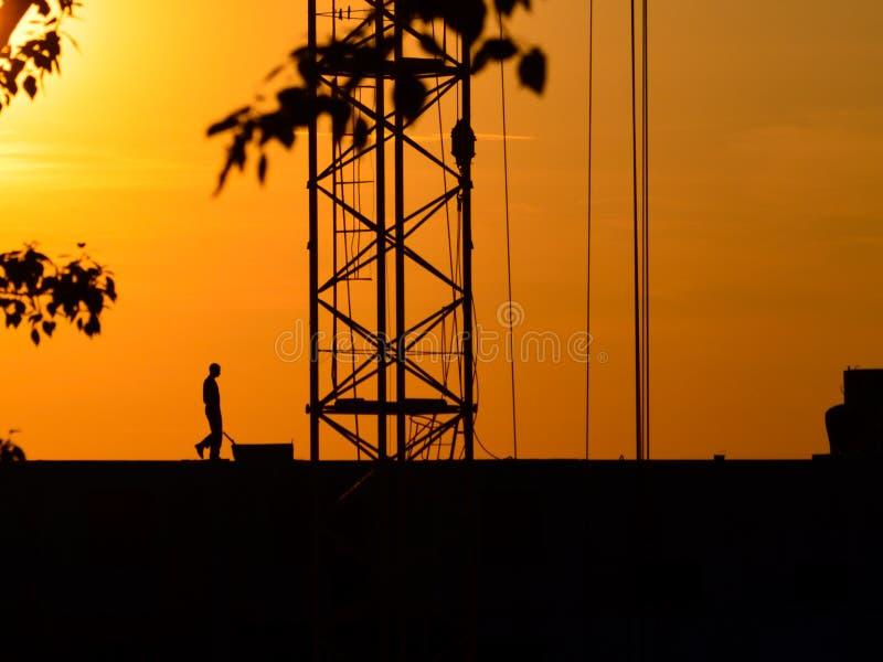 Silhouettes d'une grue et d'un travailleur de la construction sur un fond de coucher du soleil images stock