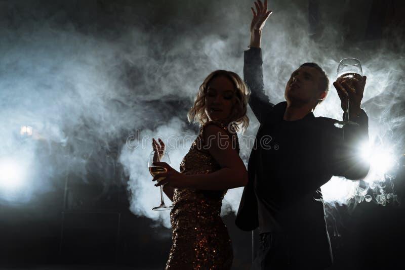 Silhouettes d'une jeune danse de couples à une partie image stock