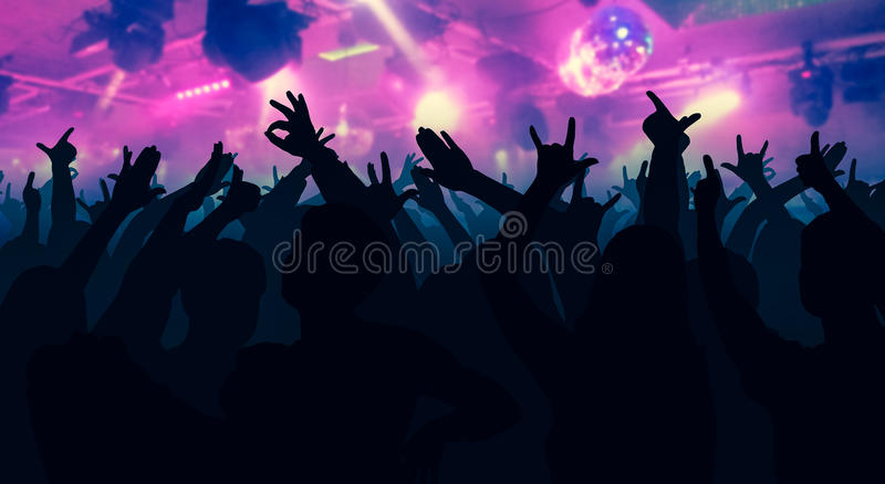 Silhouettes of dancing people in front of bright stage lights royalty free stock photography