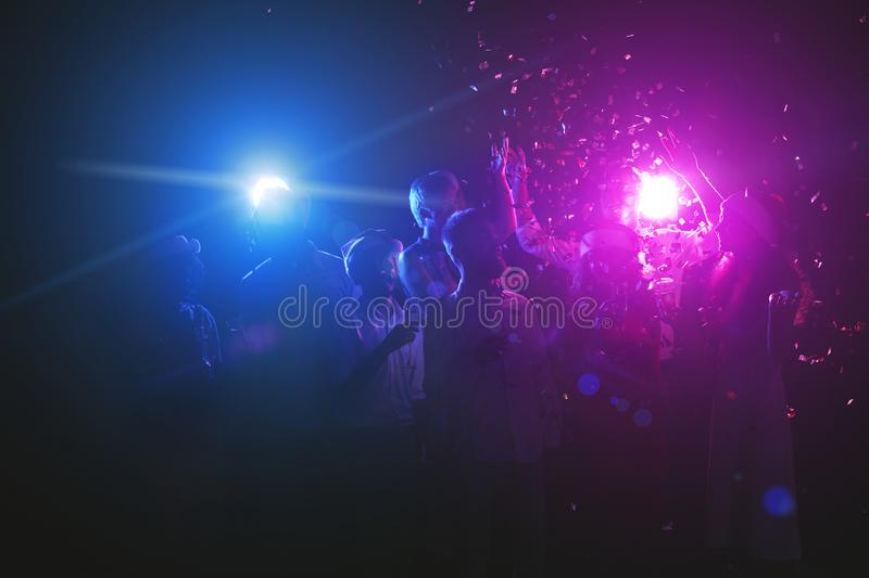 Silhouettes of dancing people having celebration at club stock photos