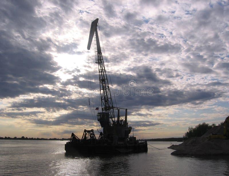 Silhouettes de barge-grue contre le ciel au coucher du soleil image stock