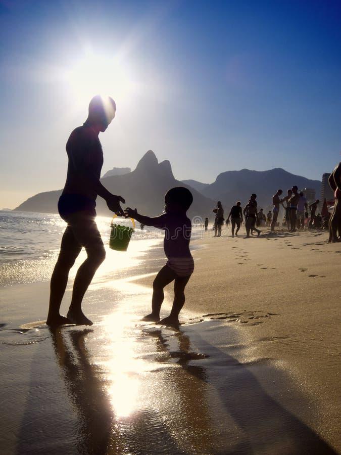 Silhouettes de coucher du soleil brésilien de plage d'Ipanema de père et d'enfant photographie stock