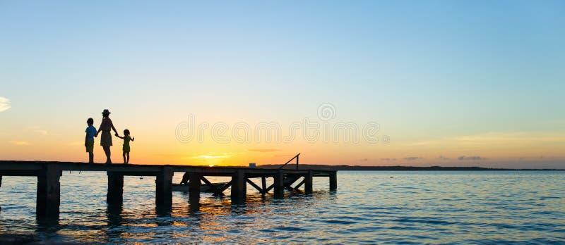 Silhouettes de coucher du soleil de famille photographie stock libre de droits