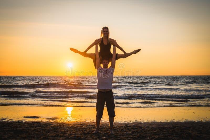 Silhouettes de deux danseurs faisant des acrobaties au coucher du soleil photos libres de droits