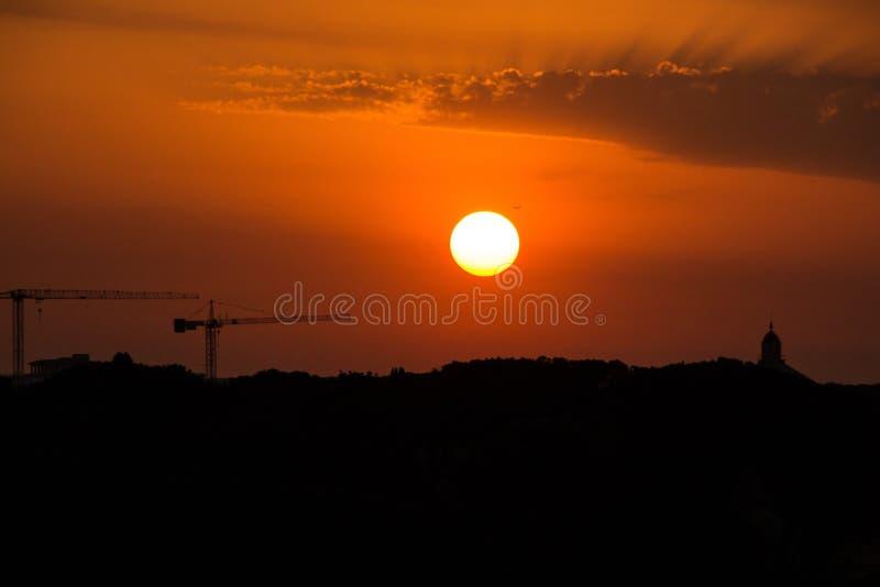 Silhouettes de deux grues de construction et le dôme de l'église sur le fond du soleil et du coucher du soleil égalisants étonnan photos libres de droits