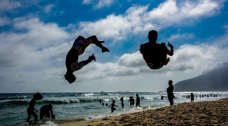 Silhouettes de deux hommes exécutant des sauts périlleux à la plage d'Ipanema images stock