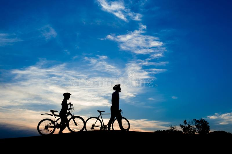 Silhouettes de jeunes ajouter aux vélos au coucher du soleil photographie stock libre de droits