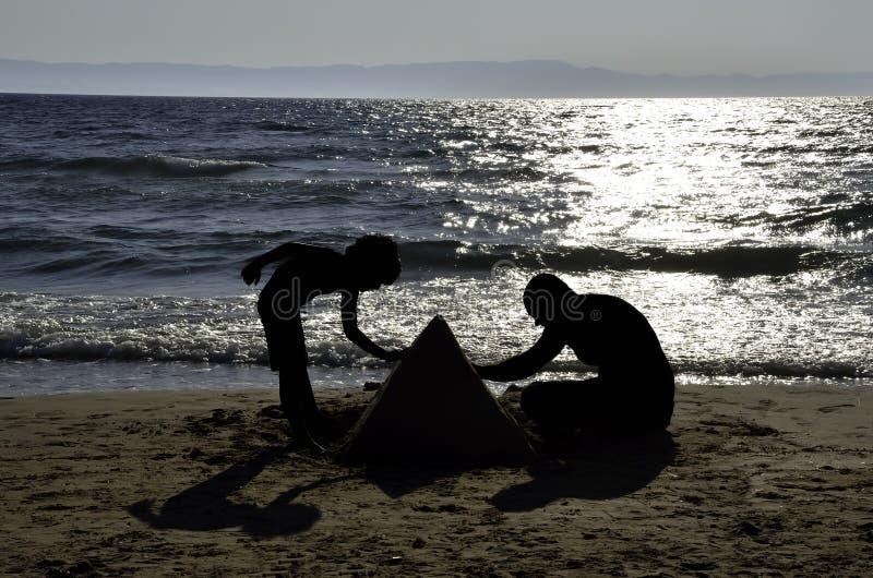 Silhouettes de l'enfant et du père jouant avec le sable sur la plage image libre de droits