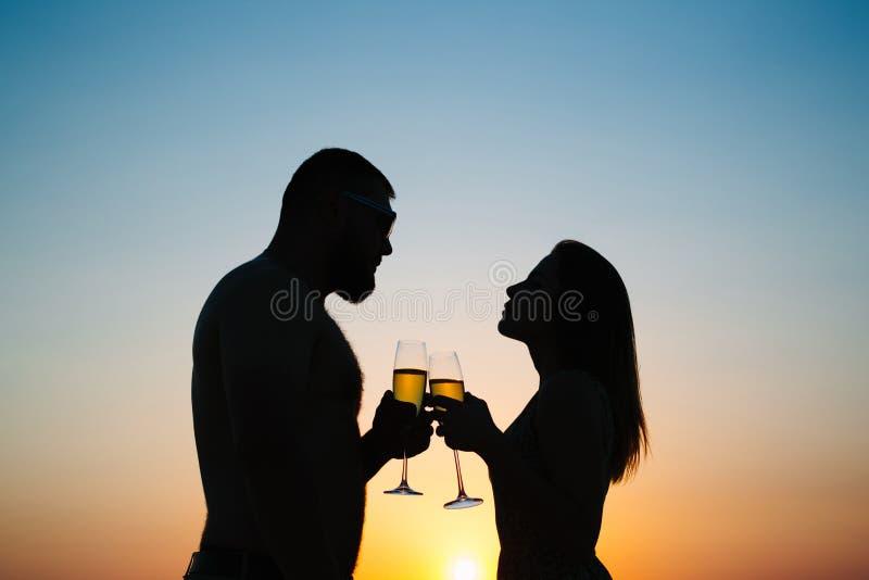 Silhouettes de l'homme et de femme au fond dramatique de ciel de coucher du soleil, photo stock