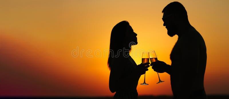 Silhouettes de l'homme et de la femme au fond dramatique de ciel de coucher du soleil, couple grillant des verres de vin dans l'a image libre de droits