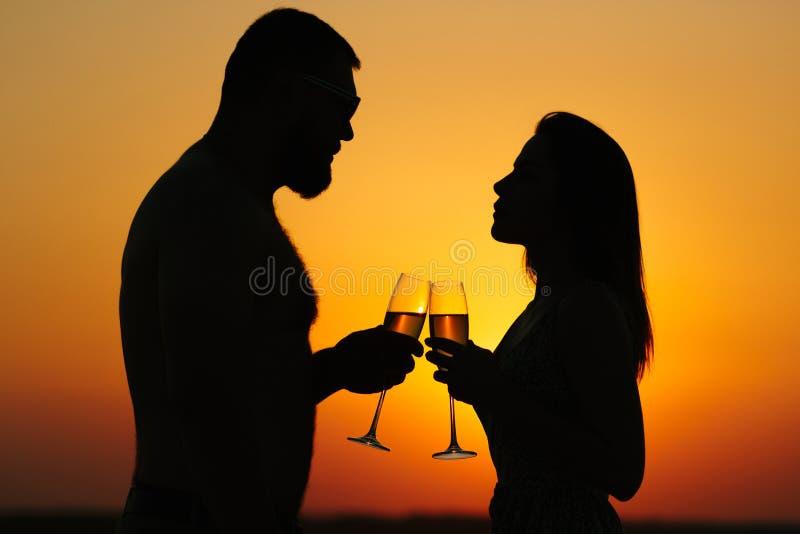 Silhouettes de l'homme et de la femme au fond dramatique de ciel de coucher du soleil, couple grillant des verres de vin dans l'a image stock