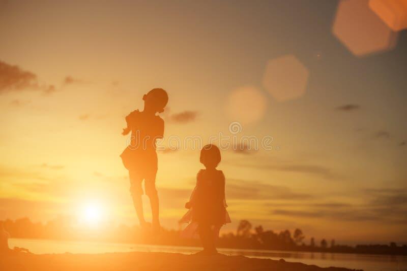 Silhouettes de la mère et de la petite fille marchant au coucher du soleil images stock