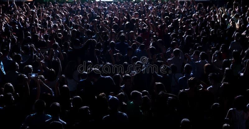 Silhouettes de la musique de concert de partie de foule heureuse photo stock
