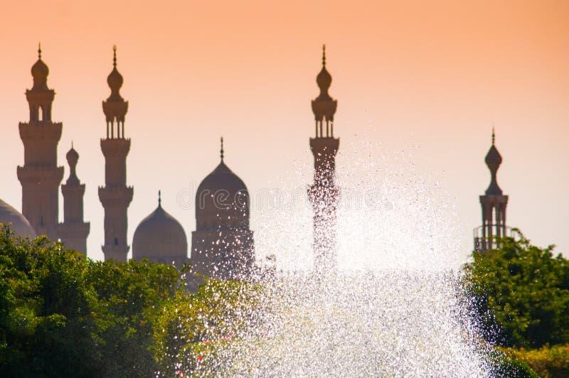 Silhouettes de mosquées contre le ciel jaune et la fontaine de scintillement au Caire photo libre de droits