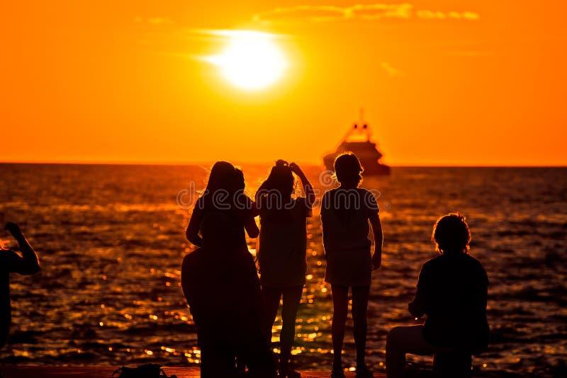 Silhouettes de personnes au coucher du soleil d'or en mer et le yacht sur l'horizon photographie stock