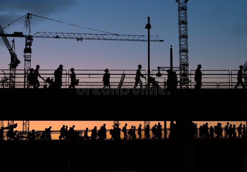 Silhouettes de pont de croisement de personnes avec le fond de ciel de coucher du soleil images libres de droits