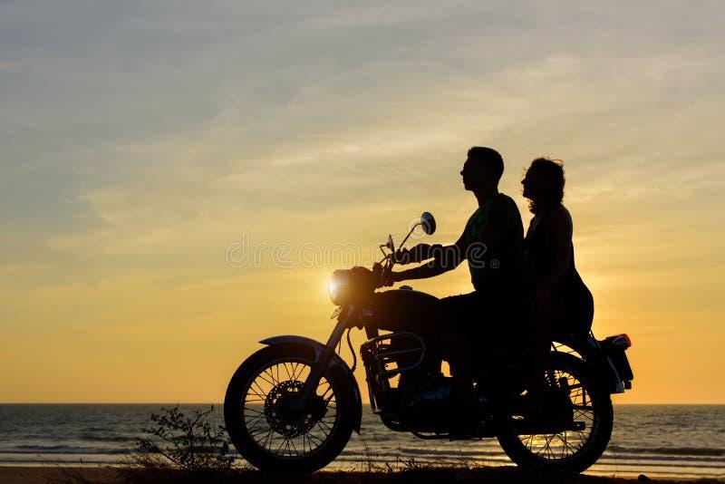 Silhouettes de type et de fille sur la moto sur le fond de coucher du soleil d'océan Les jeunes couples se reposent sur la moto,  images libres de droits