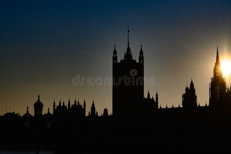 Silhouettes des Chambres du Parlement avec Victoria Tower et des poutres du soleil derrière l'Abbaye de Westminster, ville de Lon images libres de droits