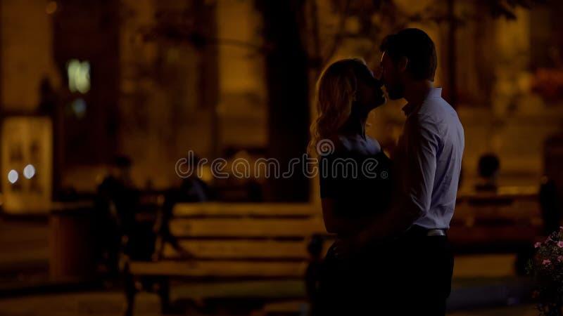 Silhouettes des couples embrassant en parc de ville, émotions se sentantes d'amour à la première date images libres de droits