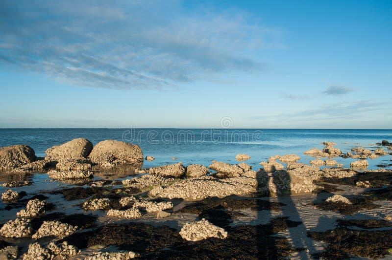 silhouettes des couples sur des roches sur le paysage de coucher du soleil à St Pierre de Quiberon - en Grande-Bretagne - en Fran photos stock