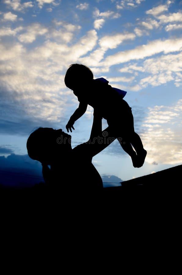 Silhouettes des femmes et de l'enfant le soir images stock