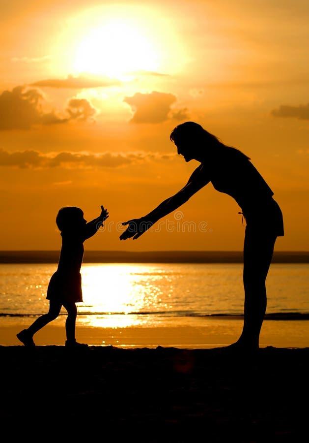 Silhouettes des femmes et de l'enfant sur le crépuscule photo libre de droits