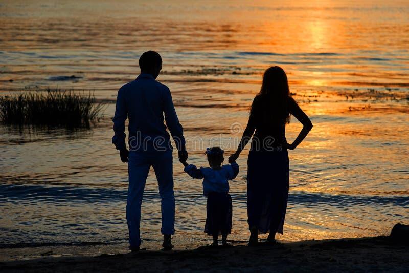 Silhouettes des parents et de l'enfant sur le fond du coucher de soleil photos stock