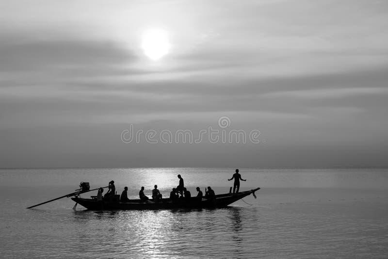 Silhouettes des personnes ayant l'amusement sur un bateau de longue queue en mer photo stock